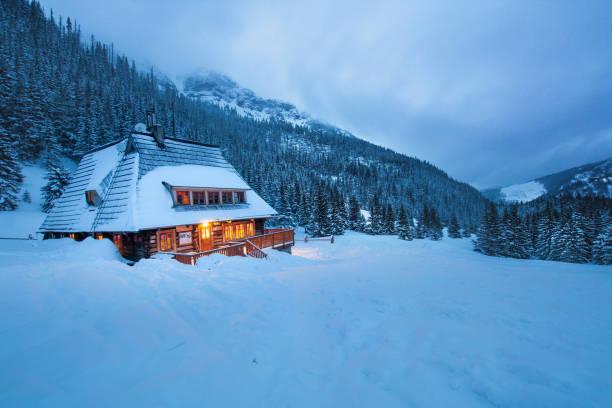 Chalet en bois illuminé au cœur de la montagne enneigée